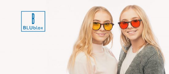 Two girls wearing BluBlox glasses next to the BluBlox logo